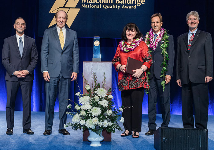 CEO Kathy Raethel and Quality Supervisor Steven Bovey accept the Malcolm Baldrige National Quality Award.